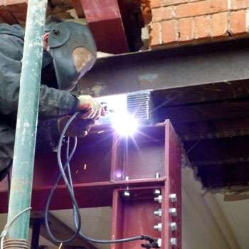 welder welding structural steel on building site with bright welding arc light